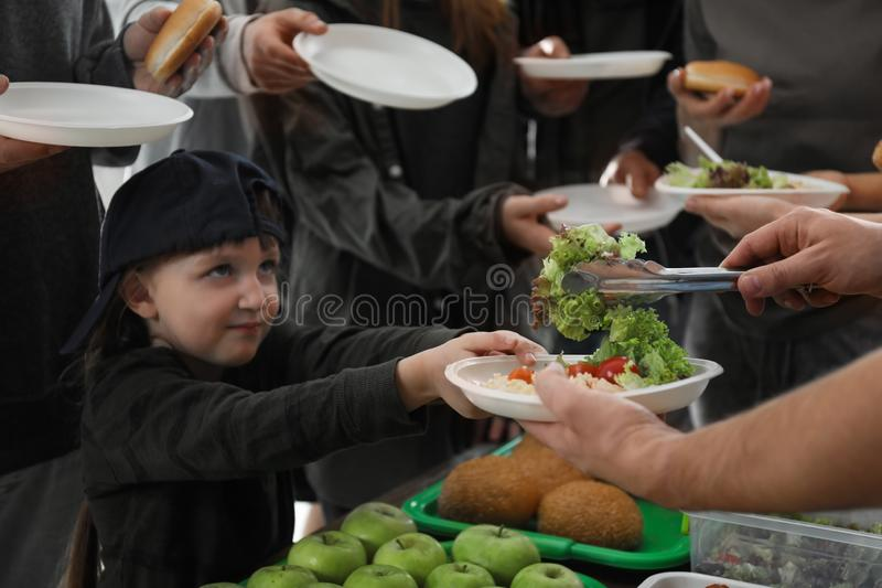 有接受食物的可怜的人民的女孩从志愿者 免版税图库摄影