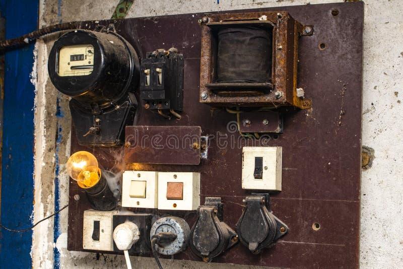 有接线和用管道输送的老内阁电气系统控制在自动化工作的小工厂 免版税库存图片