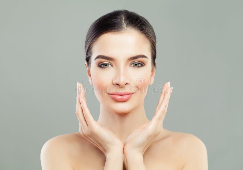 有接触她的手的健康皮肤的温泉式样妇女她的面孔 免版税库存图片