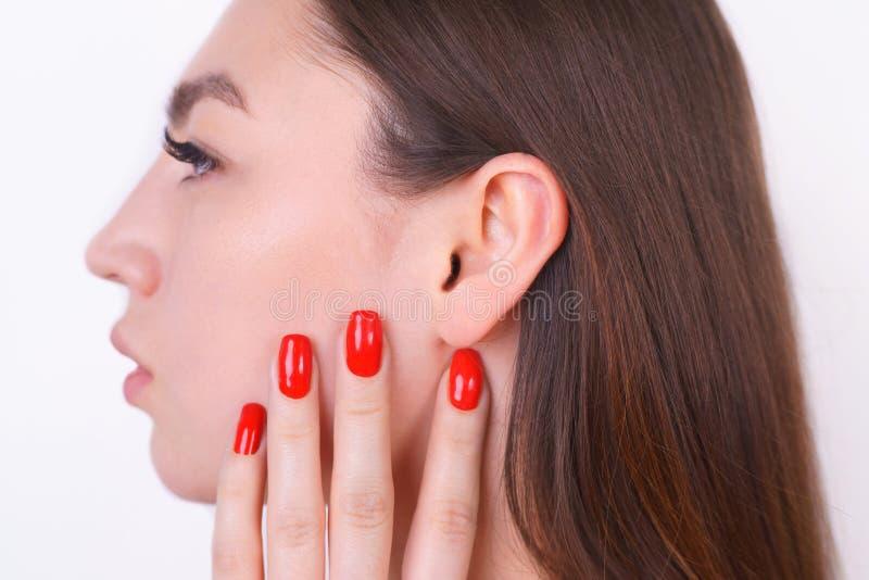 有接触她的耳朵的完善的皮肤的年轻美丽的妇女 cosmet 免版税库存照片