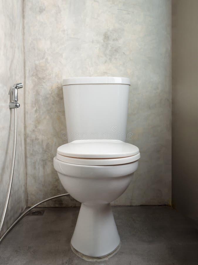 有接近的洗手间盒盖位子的白色陶瓷马桶和净身盆阵雨在灰色混凝土墙和地板卫生间里 免版税库存照片