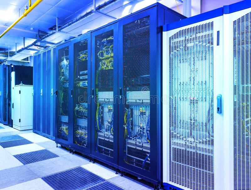有控制模块的服务器室在蓝色定调子下的机架datacenter 免版税库存照片