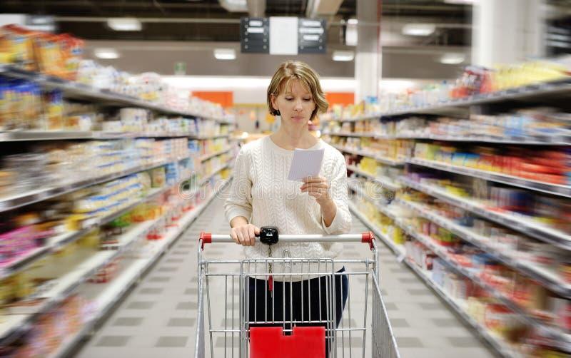 有推挤推车的购物单的妇女看物品在超级市场 免版税图库摄影