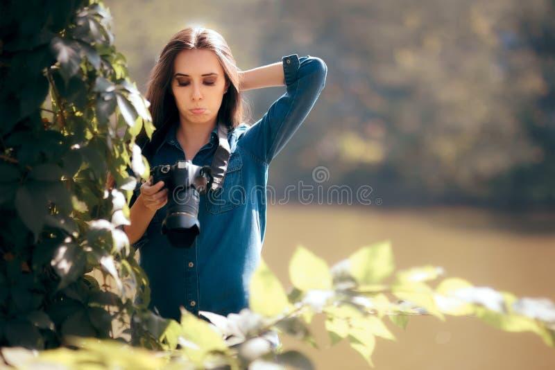 有掩藏在灌木的照相机的女性无固定职业的摄影师 免版税库存图片