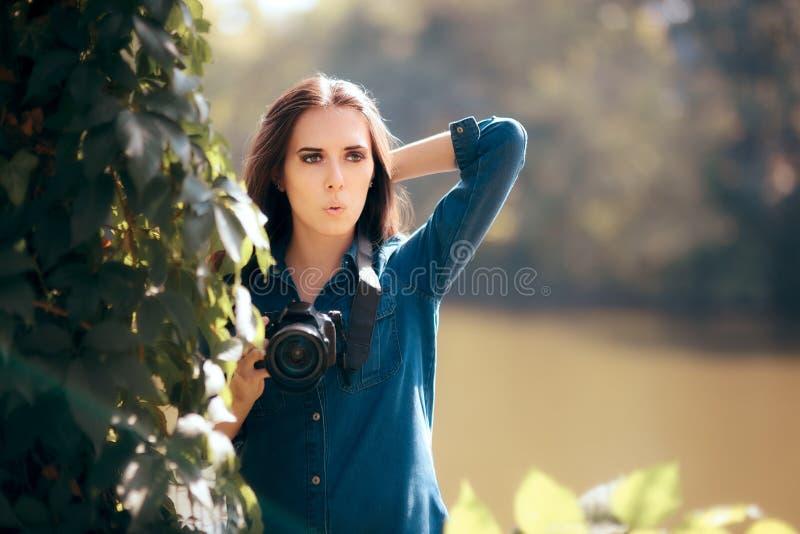 有掩藏在灌木的照相机的女性无固定职业的摄影师 库存照片