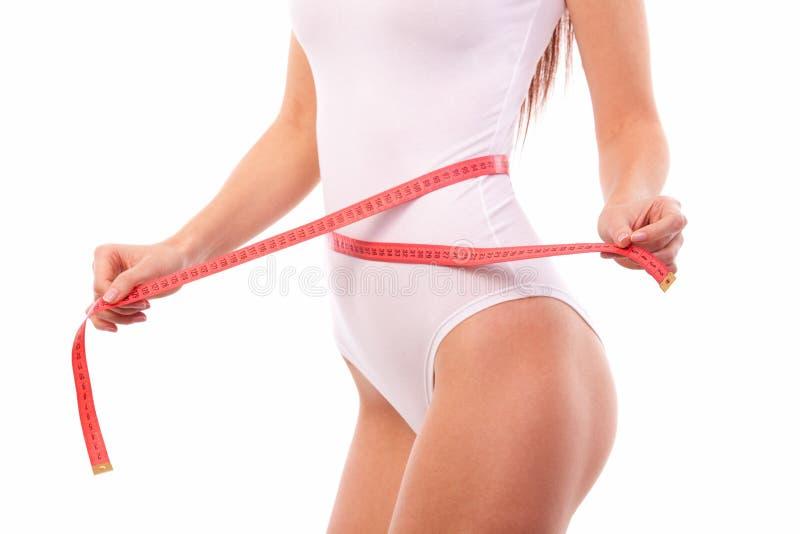 有措施磁带的妇女身体 关闭运动和美好的女性身体 被晒黑的妇女测量的腰部和臀部与测量 免版税库存照片