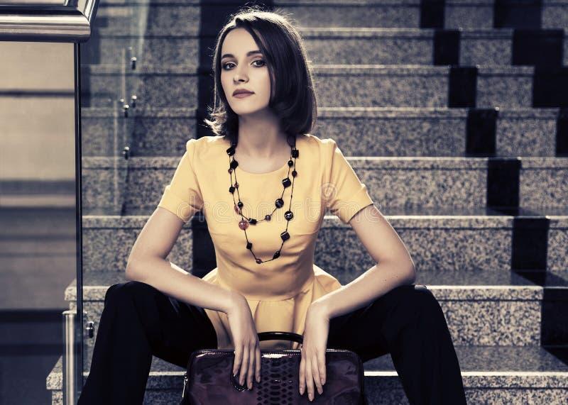 有提包的年轻时装业妇女坐步在办公室 库存图片