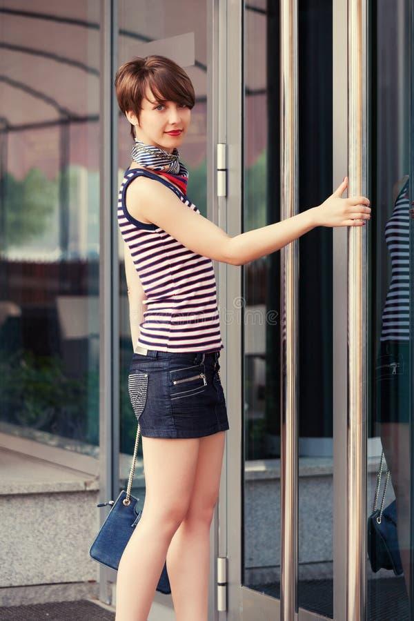 有提包的愉快的年轻时尚妇女在购物中心门旁边 免版税库存照片