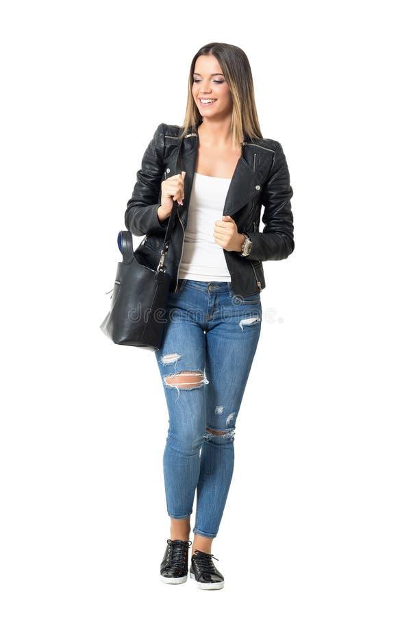 有提包的看偶然街道样式时尚的女孩微笑和下来 免版税库存图片