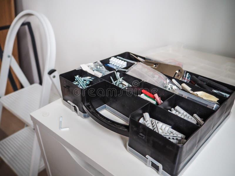 有插座和螺丝的黑塑料工具箱在内阁 免版税库存图片