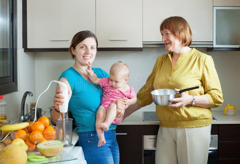 有搅拌器的愉快的妇女在厨房里 免版税库存照片