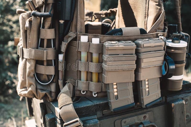有携带无线电话的军队背心,被充电的衣领,使手榴弹,光亮棍子震惊 库存照片