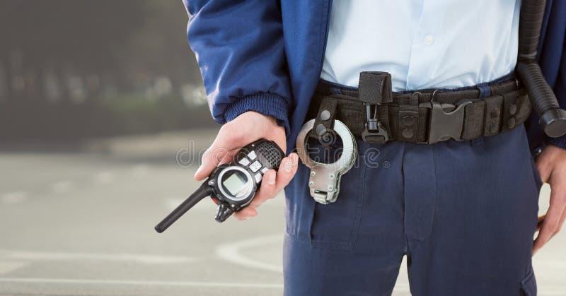 有携带无线电话的治安警卫下体反对模糊的街道 库存照片