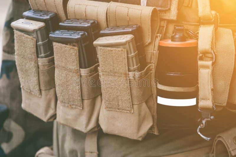 有携带无线电话被充电的衣领的军队背心使站立在一个木箱的手榴弹光亮棍子震惊弹药 库存照片