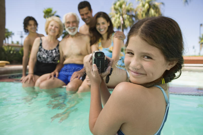 有摄象机录音家庭的女孩在游泳池 库存图片