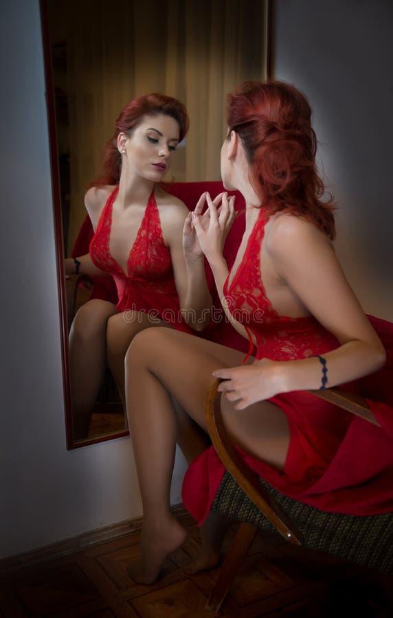 有摆在一个大墙壁镜子前面的长的红色鞋带礼服的美丽的红色头发女孩 年轻有吸引力的红头发人,侧视图 免版税图库摄影
