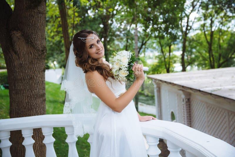 有摆在一个白色阳台的一套婚礼礼服的长的卷曲黑发的年轻美丽的新娘,微笑,拿着花束 库存照片