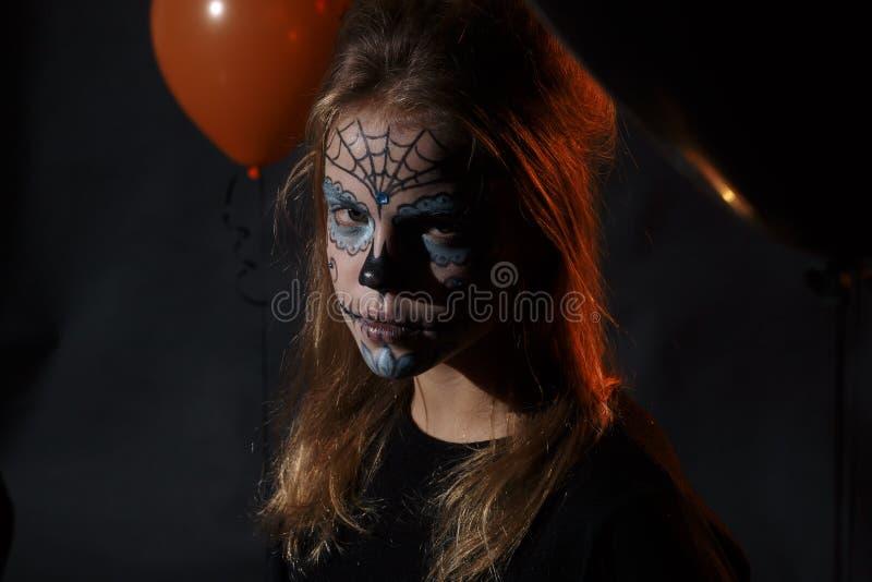 有摆在万圣夜的长的卷毛的逗人喜爱和俏丽的女孩戴一个巨大的黑和橙色帽子 图库摄影