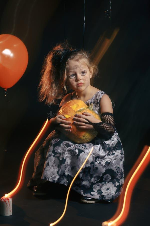 有摆在万圣夜的长的卷毛的逗人喜爱和俏丽的女孩戴一个巨大的黑和橙色帽子 库存照片