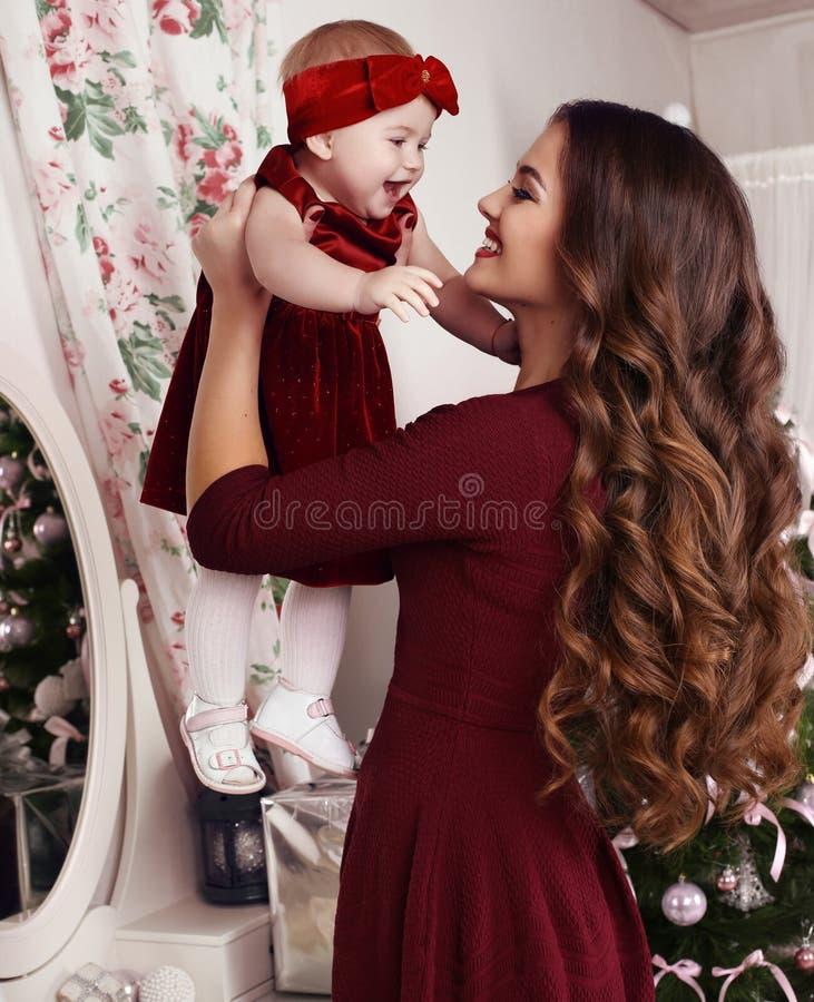 有摆在与她在圣诞树旁边的逗人喜爱的小女孩的豪华黑发的美丽的母亲 库存图片