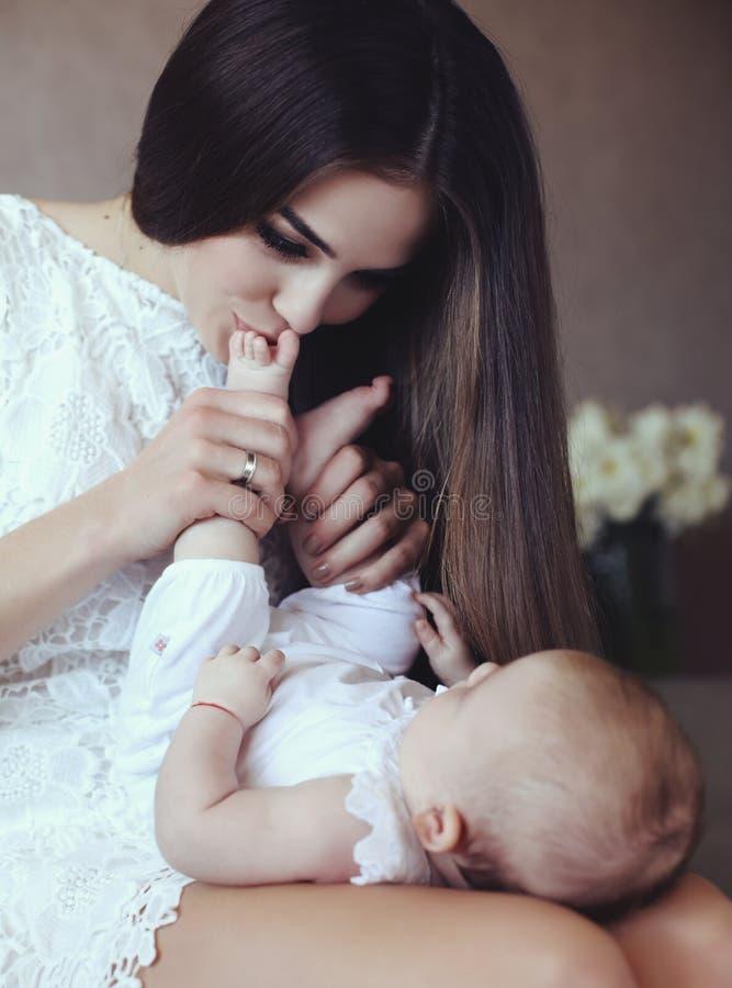 有摆在与她的小可爱的婴孩的长的黑发的美丽的年轻母亲 库存图片