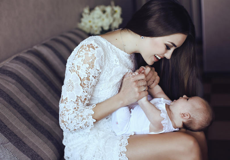 有摆在与她的小可爱的婴孩的长的黑发的美丽的年轻母亲 免版税库存照片
