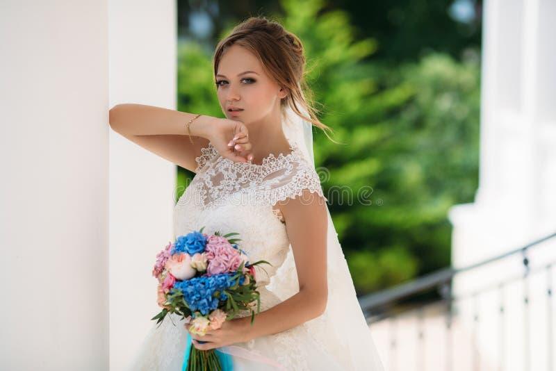 有摆在与花花束的婚礼礼服的蓝眼睛的白肤金发的新娘  模型举了她的手对她的面孔 的treadled 图库摄影