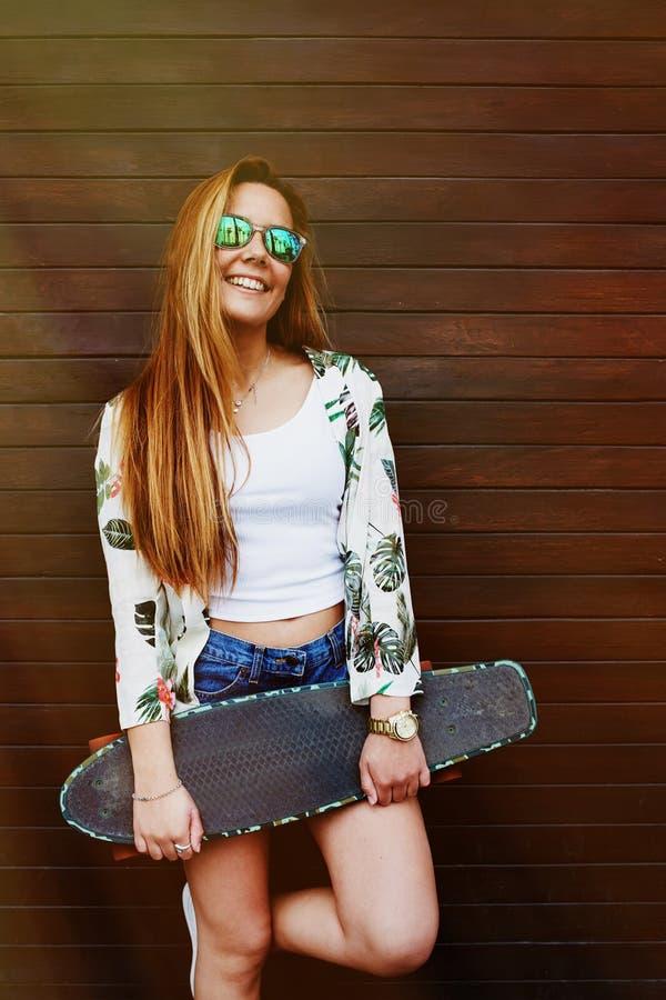 有摆在与longboard的美好的图的偶然穿戴的女性行家在夏天 免版税库存图片