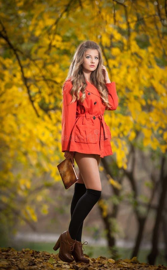 有摆在公园的橙色外套的美丽的端庄的妇女在秋天。有金发的年轻俏丽的妇女花费在秋季的时间 免版税库存照片