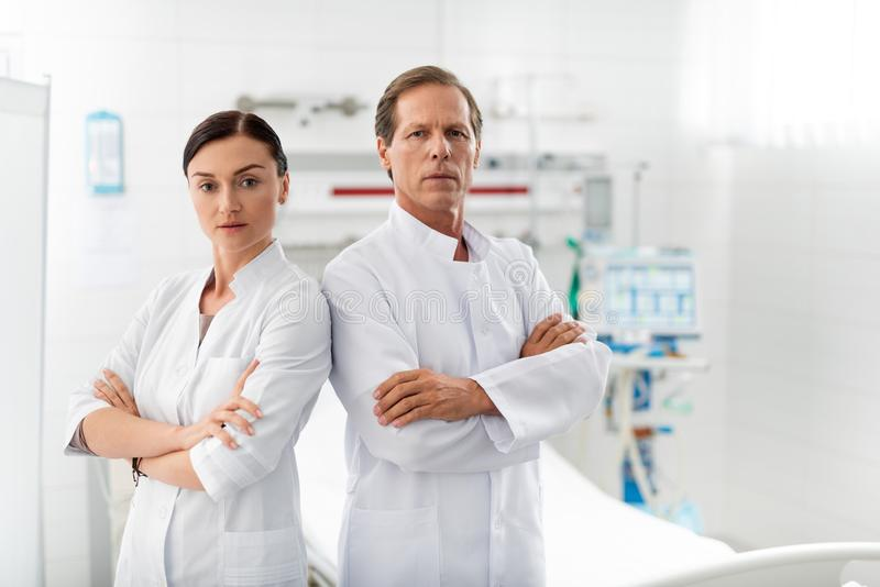 有摆在医房的横渡的胳膊的确信的医护人员 库存图片