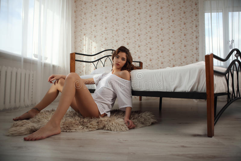 有摆在卧室的长的亭亭玉立的腿的美丽的微笑的深色的妇女 免版税库存图片