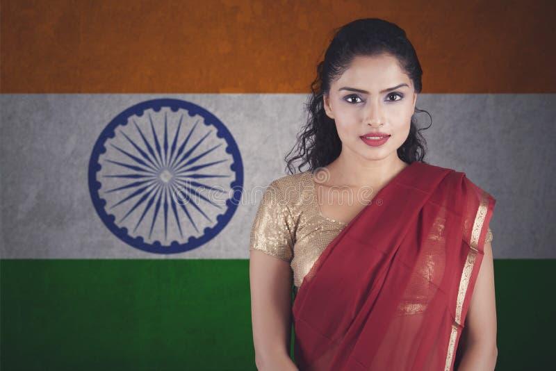 有摆在印地安旗子的莎丽服的确信的印地安妇女 免版税库存图片