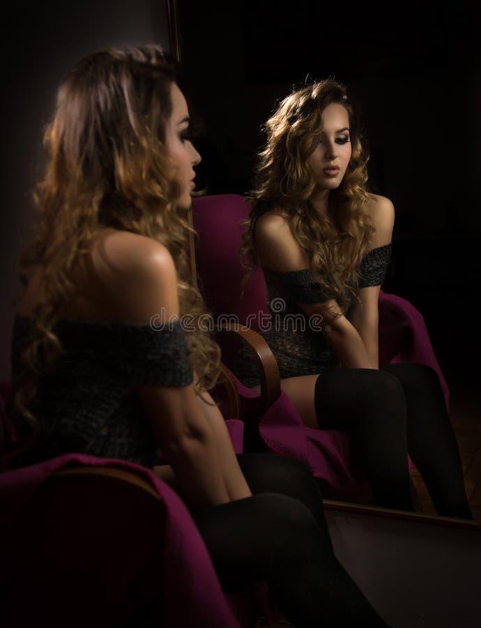 有摆在坐在镜子前面的黑长的长袜的可爱的性感的金发碧眼的女人 纵向肉欲的妇女年轻人 免版税库存图片