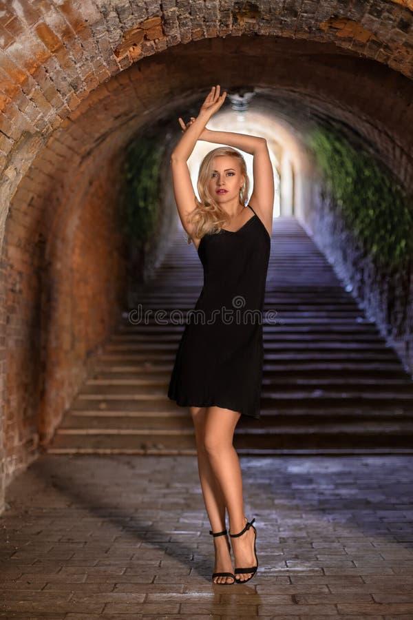 有摆在城堡隧道的完善的腿的妇女 库存照片