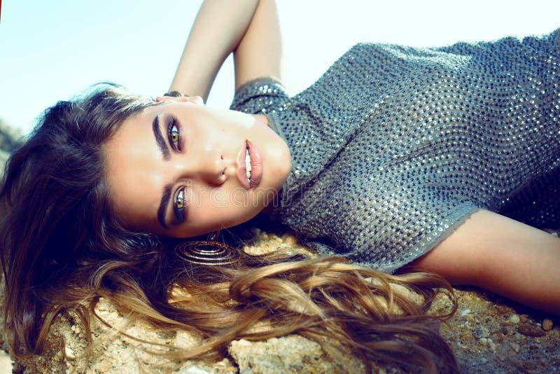 有摆在夏天海滩的黑发的美丽的魅力妇女 免版税库存图片