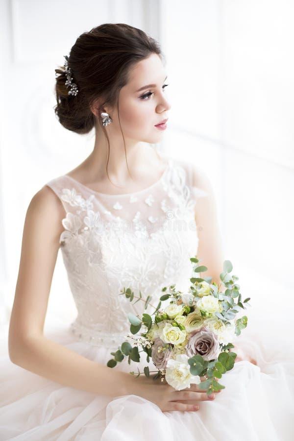 有摆在婚礼礼服的花束的美丽的深色的妇女 免版税库存图片