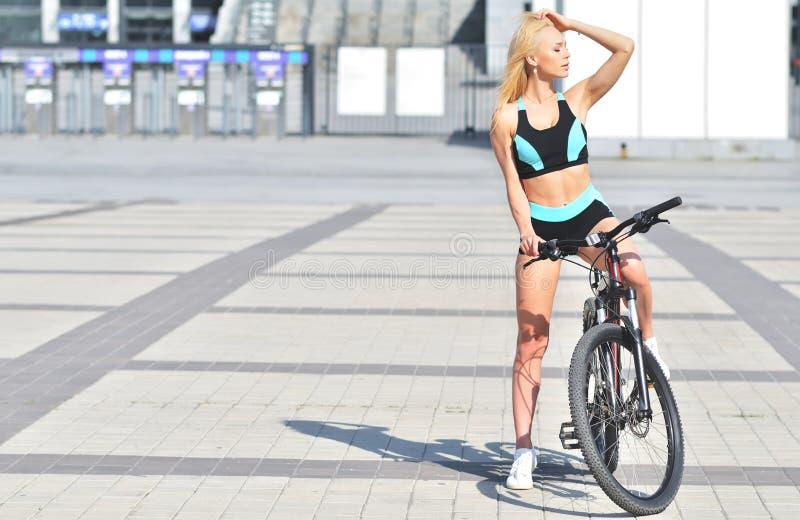 有摆在室外的长发的美丽,性感的白肤金发的妇女与自行车 免版税库存图片