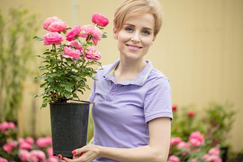有摆在庭院里的玫瑰的美丽的少妇 库存照片