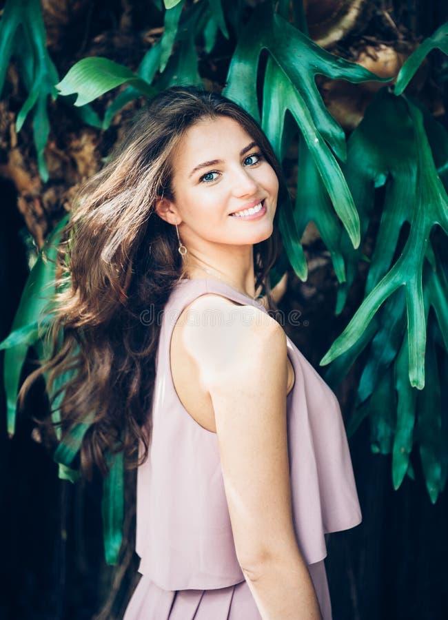 有摆在户外在热带森林里的自然牙微笑的美丽的年轻妇女 库存照片
