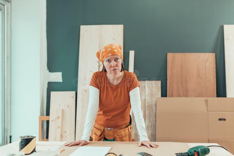 有摆在木制品车间的方巾的女性木匠 免版税图库摄影