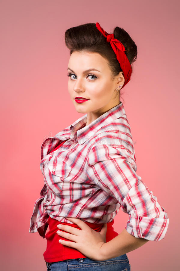 有摆在桃红色背景的针构成和发型的美丽的少妇 免版税库存照片