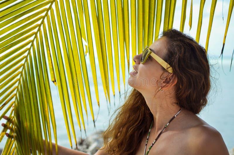 有摆在棕榈树旁边的太阳镜的女孩 库存照片