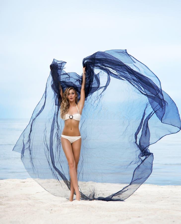 有摆在海滩的蓝色丝绸的年轻白肤金发的妇女 库存照片