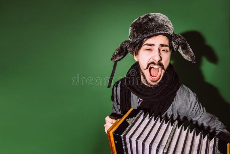 有摆在演播室的手风琴的一个非常正面人 免版税库存图片