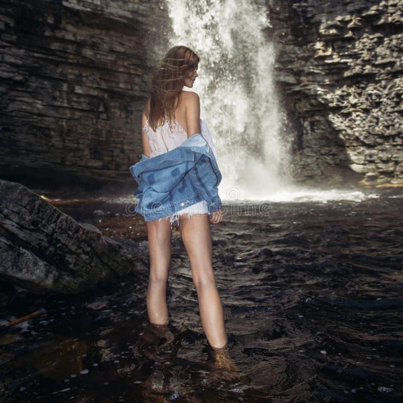 有摆在瀑布佩带的牛仔裤夹克附近的长的腿的美丽的式样女孩 库存照片