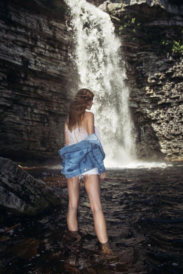 有摆在瀑布佩带的牛仔裤夹克附近的长的腿的美丽的式样女孩 库存图片
