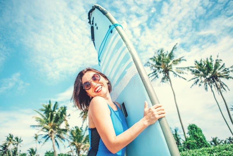 有摆在热带海滩的冲浪板的微笑的妇女 大太阳镜的冲浪者女孩有摆在海洋海滩的长的委员会的 免版税库存图片