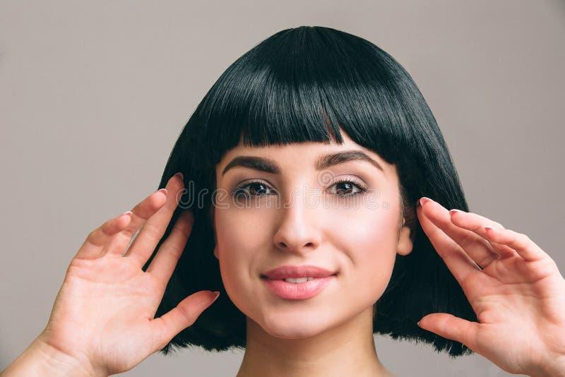 有摆在照相机的黑色头发的年轻女人 有突然移动理发的可爱的浅黑肤色的男人 式样接触它用两只手 免版税库存图片
