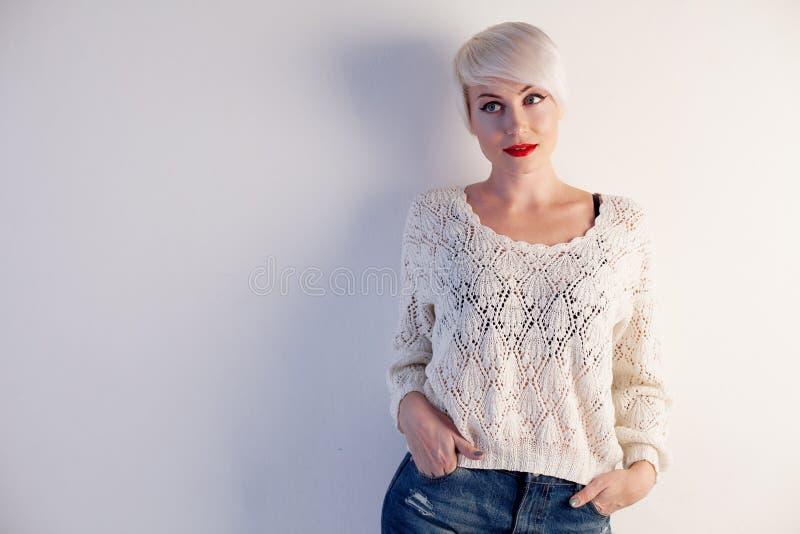 有摆在白色墙壁的短发的金发碧眼的女人 库存照片