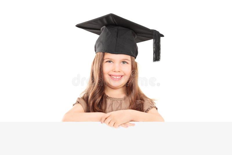 有摆在盘区后的毕业帽子的逗人喜爱的女孩 免版税图库摄影